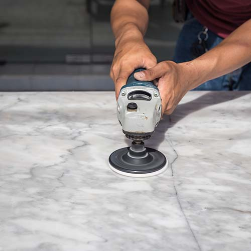 Man polishing marble table by angle grinder